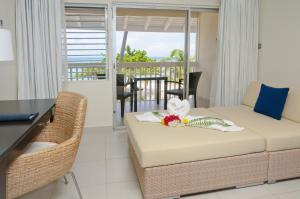 A bed or beds in a room at Radisson Grenada Beach Resort