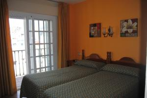 A bed or beds in a room at Hostal Italia