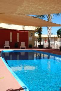 The swimming pool at or near Desert Sand Motor Inn