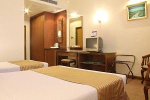 سرير أو أسرّة في غرفة في فندق بوترا كوالالمبور