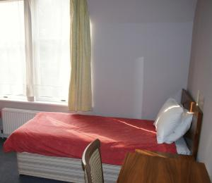 A bed or beds in a room at Kirkdale Hotel
