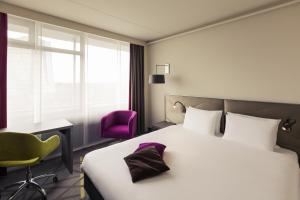 A bed or beds in a room at Mercure Hotel Groningen Martiniplaza