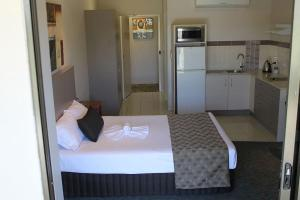 A bed or beds in a room at Emerald Executive Apartments