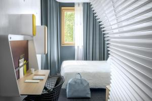 A bed or beds in a room at Okko Hotels Grenoble Jardin Hoche