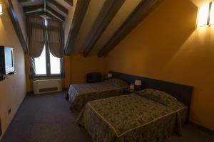 A bed or beds in a room at Malpensa Inn Hotel