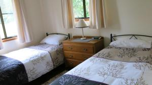 A bed or beds in a room at Ravensbourne Escape - Cedar Lodge