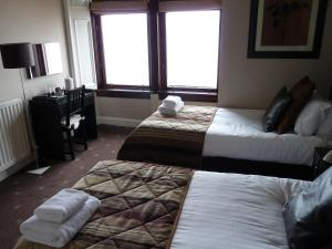 A bed or beds in a room at The Spinnaker Hotel