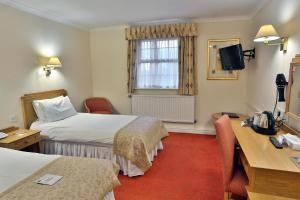 A bed or beds in a room at Reigate Manor Hotel