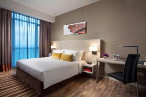 A bed or beds in a room at Citadines Uplands Kuching