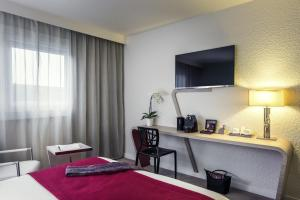 A television and/or entertainment center at Mercure Paris Le Bourget Aeroport