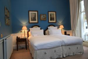 A bed or beds in a room at The Cranley Hotel