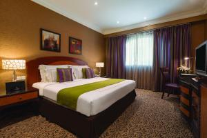 A bed or beds in a room at Wyndham Grand Regency Doha