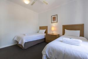 A bed or beds in a room at Forte Leeuwin Apartments