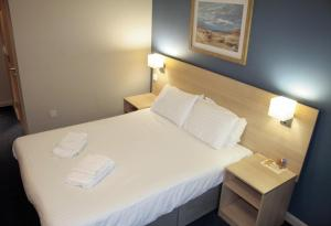 A bed or beds in a room at The Welcome Inn Rotherham/Sheffield