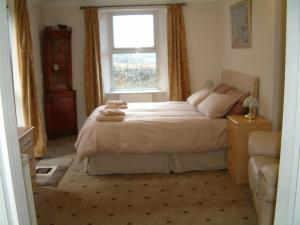 A bed or beds in a room at Harvest Home Guest House