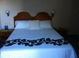 A bed or beds in a room at Hostal Victoria