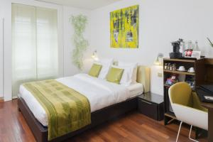 A bed or beds in a room at La Cour Des Augustins Boutique Gallery Design Hotel