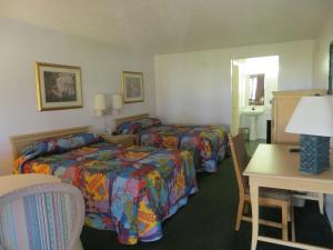 A bed or beds in a room at Magic Castle Inn & Suites Motel