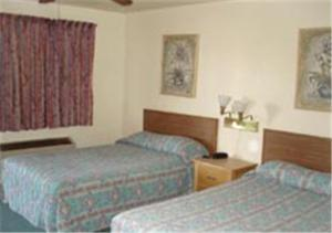 A bed or beds in a room at Miles Motel