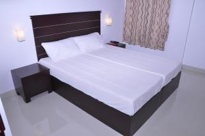 A bed or beds in a room at Pine Beach Residency