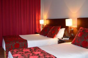A bed or beds in a room at Hotel Torres Novas