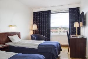 A bed or beds in a room at First Hotel Stadt