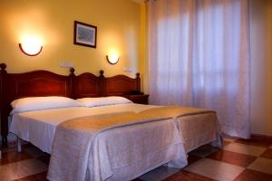 A bed or beds in a room at Hotel Sevilla