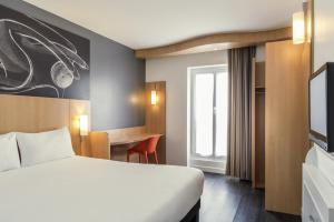 A bed or beds in a room at ibis Paris Père Lachaise