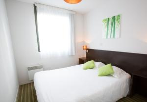 A bed or beds in a room at All Suites Bordeaux Lac - Parc des Expositions