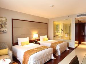 سرير أو أسرّة في غرفة في كراون بلازا كوتشي