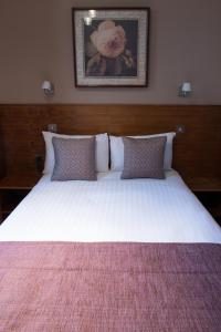 A bed or beds in a room at Garden View Hotel