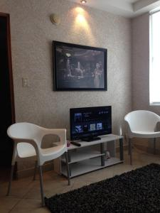 """A television and/or entertainment center at Modern apartment in San Juan """"Convention Center District Live"""" Best location"""