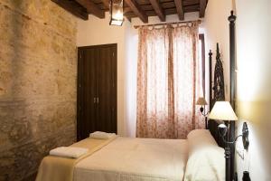 A bed or beds in a room at Hostal Palacio del Corregidor