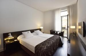 A bed or beds in a room at Hospes Palau de La Mar