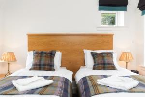 A bed or beds in a room at Elderburn Lodges