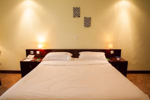 A bed or beds in a room at Gorillas Lake Kivu Hotel