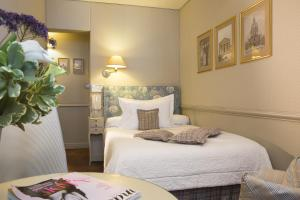 A bed or beds in a room at Hotel du Champ de Mars