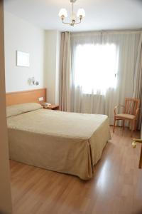 A bed or beds in a room at Aparthotel Sercotel Huesca