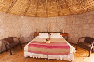 A bed or beds in a room at Ckamur Atacama Ethno Lodge & Spa