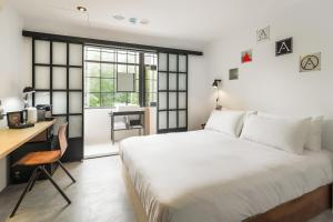 A bed or beds in a room at Art'otel Ximending Taipei