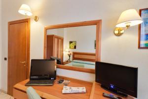 Uma TV ou centro de entretenimento em Hotel Mia Cara