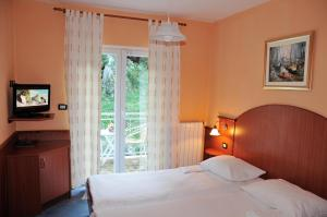 A bed or beds in a room at Hotel Pansion Stanger