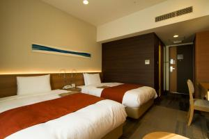 A bed or beds in a room at Hotel Sunroute Chiba