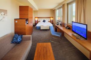 A bed or beds in a room at Mövenpick Hotel & Casino Geneva