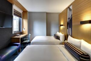 A bed or beds in a room at Aloft Brooklyn