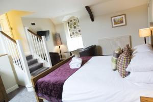 A bed or beds in a room at The Colesbourne Inn
