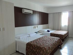 A bed or beds in a room at Apartamento Le Jardin - Suítes para Temporada