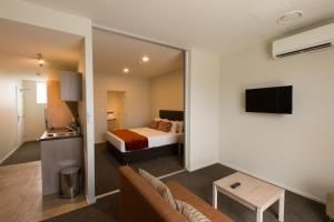 A bed or beds in a room at Ramada Suites by Wyndham Christchurch City
