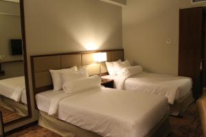 A bed or beds in a room at I Hotel Baloi Batam