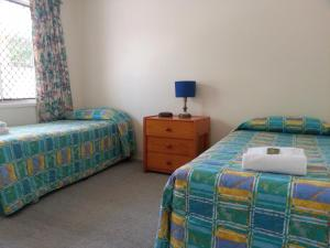 A bed or beds in a room at Sandy Court Holiday Units